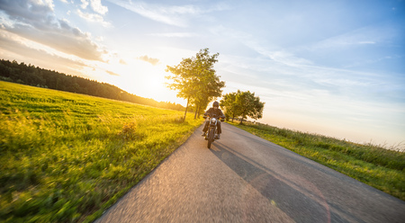 Foto de Dark motorbiker riding high power motorbike in nature with beautiful sunset light. Travel and transportation. Freedom of motorbike riding - Imagen libre de derechos
