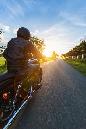 Foto de Dark motorbiker riding high power motorbike in nature with beautiful sunset light. Travel and transportation. Freedom of motorbike riding - Imagen libre de derechos