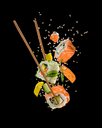 Photo for Sushi pieces placed between chopsticks, separated on black background. Popular sushi food. - Royalty Free Image