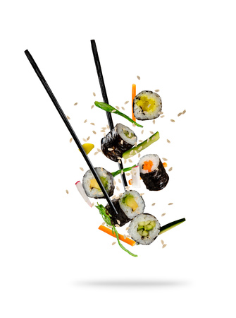 Foto de Sushi pieces placed between chopsticks, separated on white background. Popular sushi food. - Imagen libre de derechos