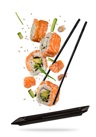 Foto de Sushi pieces placed between chopsticks, separated on white background. Popular sushi food. Very high resolution image - Imagen libre de derechos