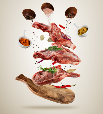 Photo for Flying pieces of raw pork steaks, with ingredients for cooking, served on woodenboard. Concept of food preparation in low gravity mode. Separated on soft background. High resolution image - Royalty Free Image