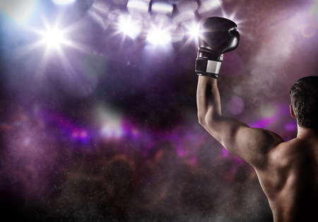 Foto de Close-up of man boxer with raised hand in victory gesture. Concept of hard sport, glory and success. Free space for text. High resolution image - Imagen libre de derechos