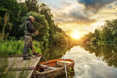 Photo for Sport fisherman hunting predator fish from wooden pier. Outdoor fishing in river during sunrise. Hunting and hobby sport. - Royalty Free Image