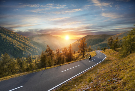 Foto de Motorcycle driver riding in Alpine highway,  Nockalmstrasse, Austria, Europe. Outdoor photography, mountain landscape. Travel and sport photography. Speed and freedom concept - Imagen libre de derechos