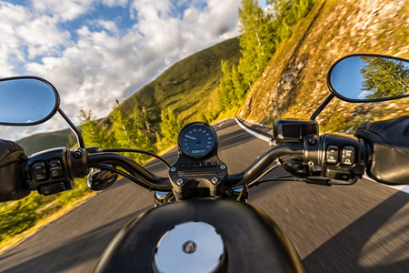Foto de Detail of motorcycle handlebars. View from driver perspective, beautiful Alpine landscape in sunset light. Travel and sport photography in outdoor. Speed and freedom concept - Imagen libre de derechos