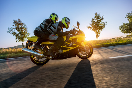 Foto per Motorbikers on sports motorbike riding in sunset. Outdoor photography, European landscape. Travel and sport photography. Speed and freedom concept - Immagine Royalty Free