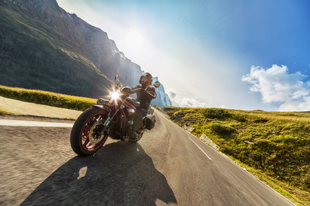 Foto de Motorcycle driver riding in Alpine highway,  Hochalpenstrasse, Austria, Europe. Outdoor photography, mountain landscape. Travel and sport photography. Speed and freedom concept - Imagen libre de derechos