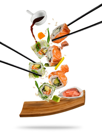 Photo for Sushi pieces placed between chopsticks, separated on white background. Popular sushi food. Very high resolution image - Royalty Free Image