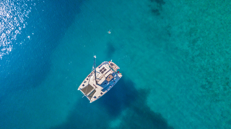 Foto de Aerial view of catamaran anchoring on coral reef. Bird eye view, water sport theme. - Imagen libre de derechos