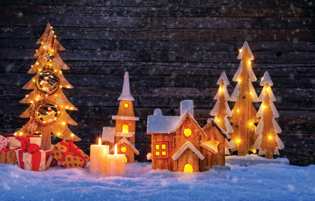 Foto de Christmas backgound with illuminated wooden village and christmas tree. Dark wooden background with free space for text. Celebration of christmas - Imagen libre de derechos