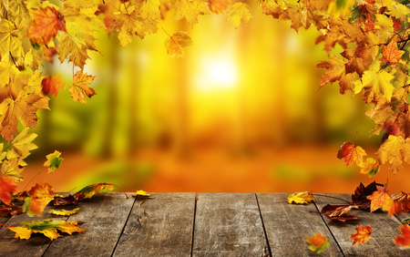 Photo for Autumn background with falling leaves and empty wooden table,  ideal for product placement or free space for text. Seasonal abstract vivid colored background - Royalty Free Image