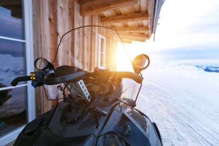 Photo for Closeup of snowmobile parking next to log cabin in mountains. Winter outdoor snow activities - Royalty Free Image