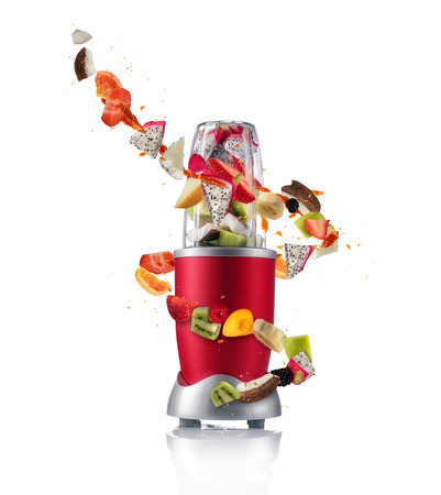 Foto de Smoothie maker mixer with pieces of fruit ingredients, isolated on white background. Healthy drink and lifestyle - Imagen libre de derechos