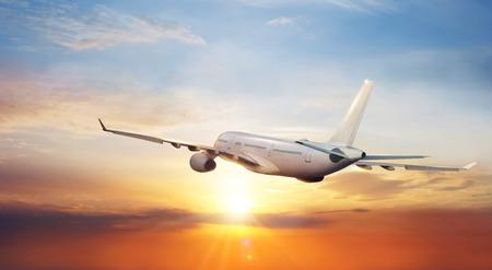 Foto de Big commercial airplane flying above clouds in sunset light. Travel and business theme. - Imagen libre de derechos