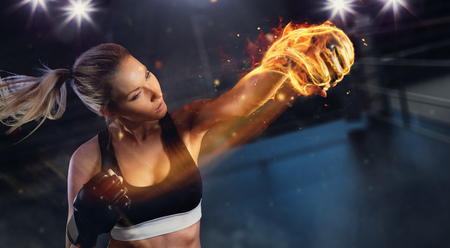 Photo for Young blond woman with fire fist hitting the target. Concept of hard work and motivation, boxing arena on background. Very high resolution image - Royalty Free Image