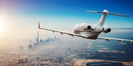 Foto de Luxury private jetliner flying above Dubai city, UAE. Modern and fastest mode of transportation, symbol of luxury and business traveling. - Imagen libre de derechos