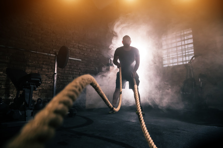 Foto de Young man doing hard exercise workout in gym interior with rope waveing. Cinematic mood with dust, dramatic lightning and smoke. Active and healthy lifestyle. - Imagen libre de derechos