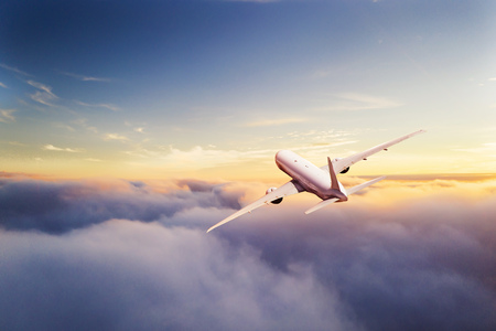 Foto de Passengers commercial airplane flying above clouds in sunset light. Concept of fast travel, holidays and business. - Imagen libre de derechos