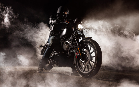 Foto de Dark motorcycle driver in fog. Wallpaper design of high power motorbike - Imagen libre de derechos