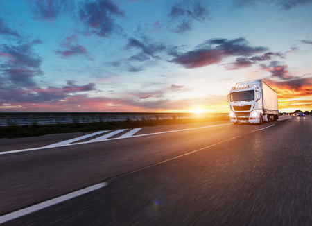 Photo pour Loaded European truck on motorway in beautiful sunset light. On the road transportation and cargo. - image libre de droit