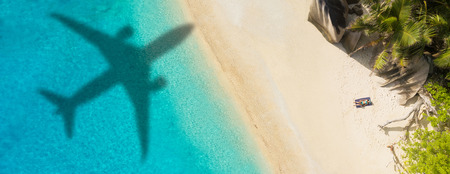 Photo pour Concept of airplane travel to exotic destination with shadow of commercial airplane flying above beautiful tropical beach. - image libre de droit