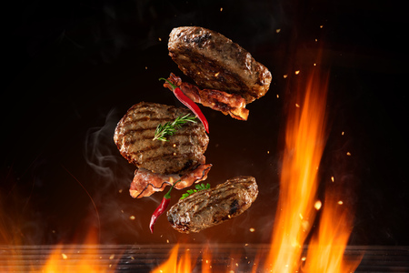 Photo pour Flying beef hamburgers pieces above burning grill grid, isolated on black backround. Barbecue and grill concept - image libre de droit