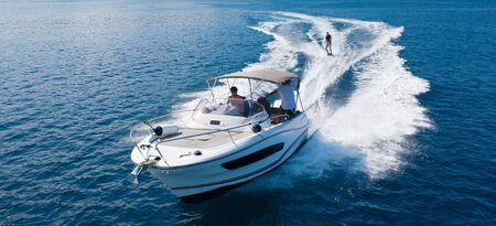 Foto de Speedboat with wakeboard rider on open sea. Leasure activities and adrenalin sport concept - Imagen libre de derechos