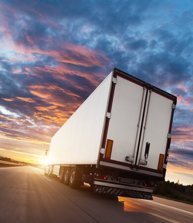 Photo pour Backview of european truck vehicle on motorway with dramatic sunset light. Cargo transportation and supply theme. - image libre de droit