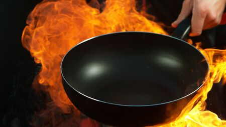 Foto de Closeup of chef holding empty wok pan with flames. Isolated on black background - Imagen libre de derechos