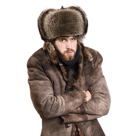 Foto de Young bearded man in the coat and earflaps hat, feel cold, isolated on a white background - Imagen libre de derechos