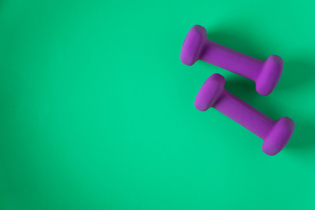 Foto de Fitness equipment with womens purple weights/ dumbbells isolated on a teal green background with copyspace (aka empty text space). - Imagen libre de derechos