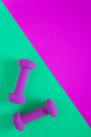 Foto de Fitness equipment with womens purple weights/ dumbbells isolated on a teal green and fuschia magenta background with copyspace (aka empty text space). - Imagen libre de derechos
