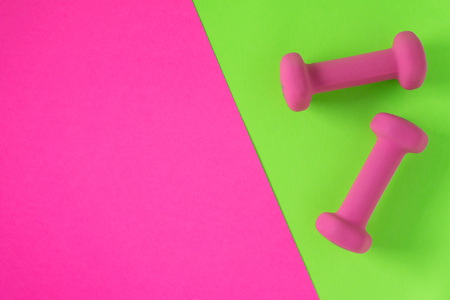 Foto de Fitness equipment with womens pink weights/ dumbbells isolated on a lime green and hot pink background with copyspace (aka empty text space). - Imagen libre de derechos
