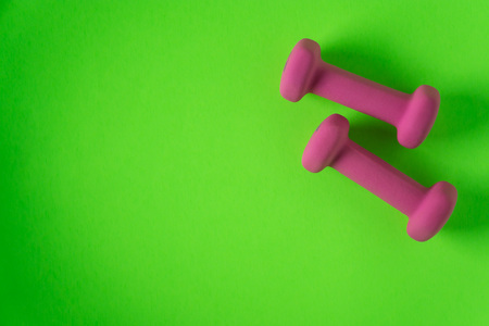 Foto de Fitness equipment with womens pink weights/ dumbbells isolated on a lime green background with copyspace (aka empty text space). - Imagen libre de derechos