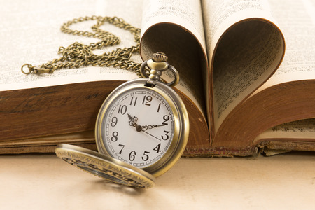 Foto de Vintage  antique pocket watch and heart of the book's pages - Imagen libre de derechos