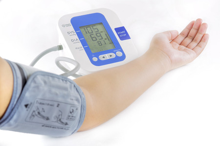 Foto de Show how to measure blood pressure with electronic blood pressure meter on arm and hand of female - Imagen libre de derechos