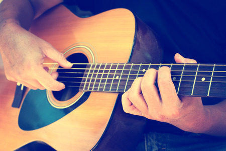Photo for Details of performer man hands playing acoustic guitar musical, vintage retro photo - Royalty Free Image