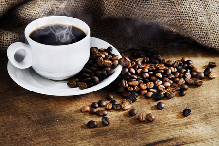 Photo pour Hot Coffee cup and roast coffee beans on a wooden table. Dark background - image libre de droit