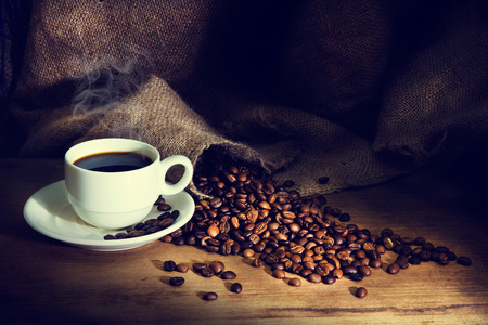 Foto de Coffee cup and coffee beans on a wooden table and sack background,Vintage color tone - Imagen libre de derechos