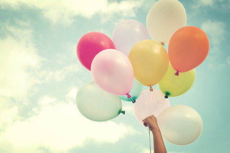 Foto de Girl hand holding multicolored balloons done with a retro vintage filter effect, concept of happy birth day in summer and wedding honeymoon party (Vintage color tone) - Imagen libre de derechos