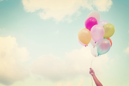 Photo pour Girl hand holding multicolored balloons done with a retro vintage  - image libre de droit