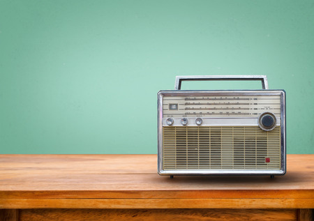 Photo pour Old retro radio on table with vintage green eye light background - image libre de droit