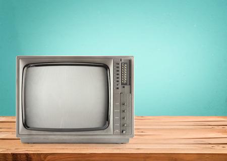 Photo pour Retro Television on wood table with vintage aquamarine wall background - image libre de droit