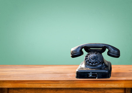 Photo pour Retro black telephone on wood table with vintage green eye light wall background - image libre de droit
