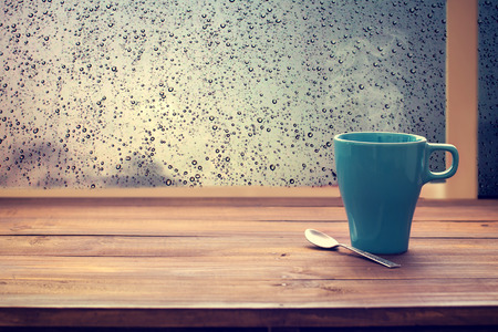 Hot coffee cup on wood table with raindrop window (vintage color tone)