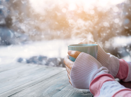 Photo pour Side view of female hand holding hot cup of coffee in winter - image libre de droit