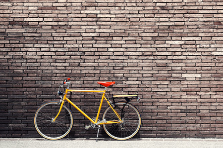 Photo pour Retro bicycle on roadside with vintage brick wall background - image libre de droit