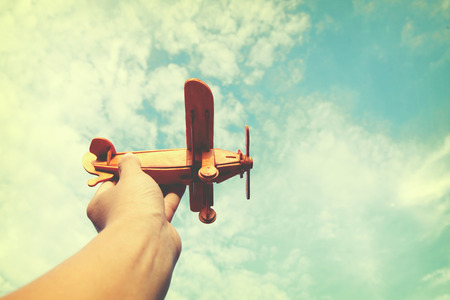 Photo pour Hands of children holding a toy plane and have dreams wants to be a pilot. - image libre de droit