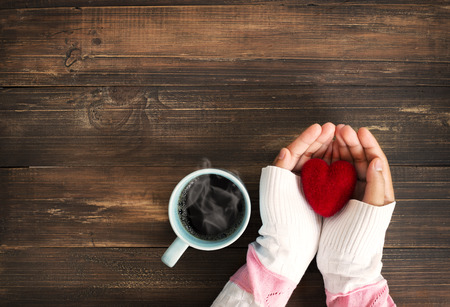 Photo pour Above view of female hand holding red heart with hot cup of coffee on wood table. Photo in vintage color image style. - image libre de droit